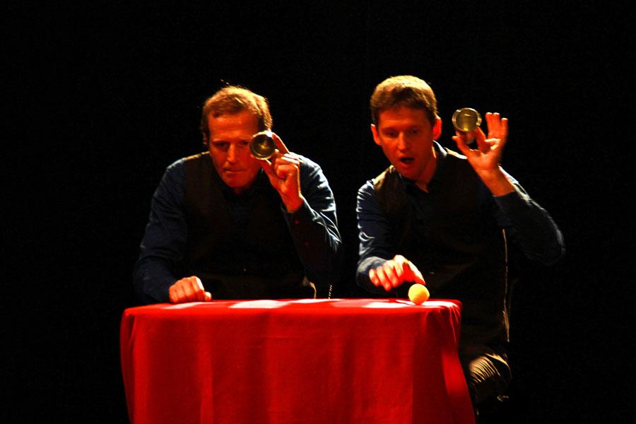 Deux magiciens à table soulèvent un goblet et l'un d'eux révèle une balle jaune