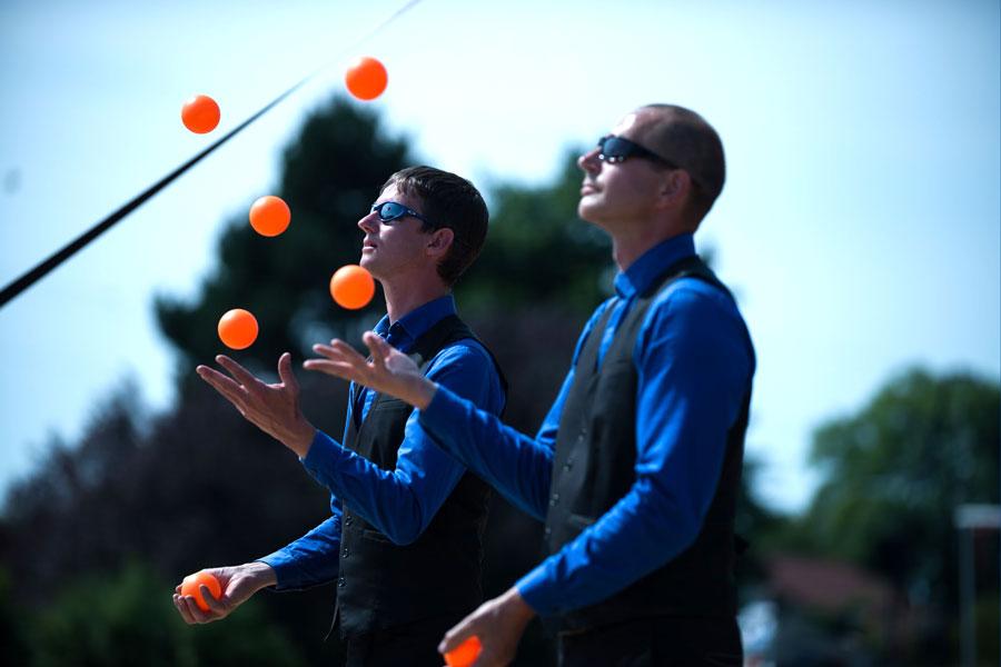 Deux jongleurs côte à côte avec 5 balles chacun jonglent face au soleil avec des lunettes de soleil